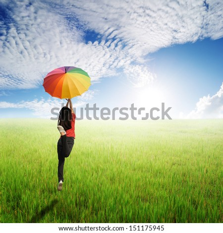 Red woman holding multicolored umbrella in green grass field and cloud sky