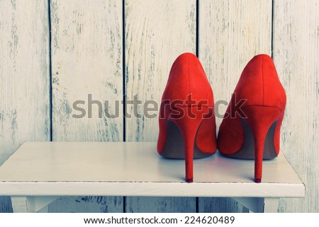 Red women shoes on wooden background - stock photo