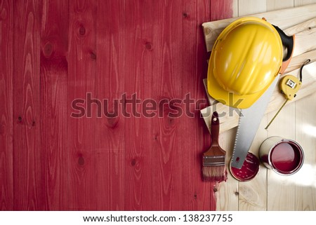 red wood floor with a brush, paint, tools and helmet - stock photo