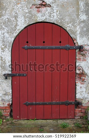 Red wooden, arched medieval door with lock