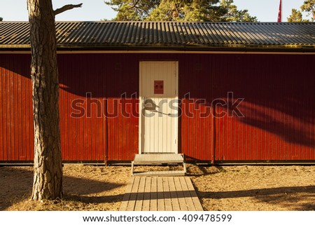 red wooden beachhouse with white door at a beach in sweden