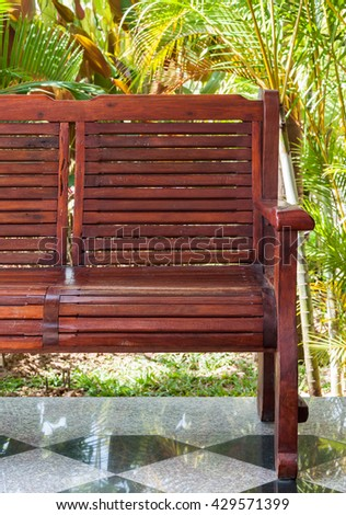 Red wooden bench on the patio near the small garden of countryside house. - stock photo