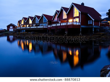 Red wooden cabins at campsite by the fjord in Molde, Norway - stock photo