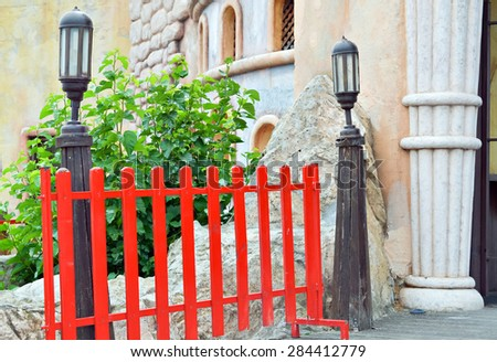 Red wooden fence on the entrance of children playground