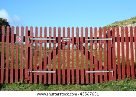 red wooden fence with a gate - stock photo