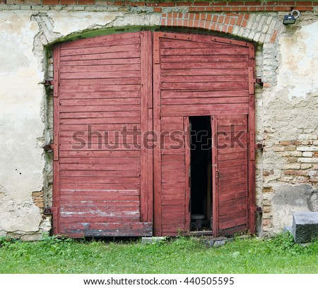 Red wooden gate of the old  rustic shed stable constructed at the beginning of the 19th century