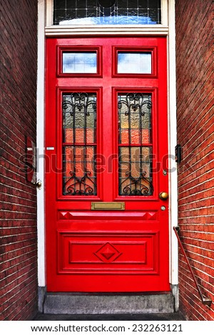 Red wooden glass door of a red brick classical building, Europe. Architectural theme. Photo in retro style. Paper texture. Aged textured photo in retro style - stock photo