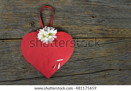red wooden heart on rustic barn wood with daisy bouquet and polka dot ribbon