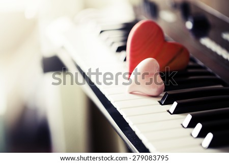 Red wooden hearts on a piano keyboard - stock photo