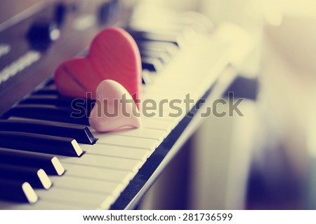Red wooden hearts on a piano keyboard/ selective focus - stock photo