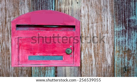 red wooden mail box on wooden wall - stock photo