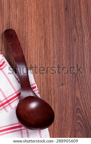 red wooden spoon on a napkin in a cage on wooden background - stock photo