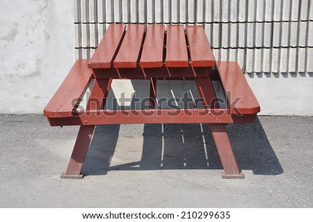 Red wooden table and benches - stock photo