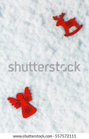 Red wooden toy angel on white snow