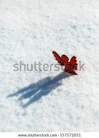 Red wooden toy angel with shadow on white snow