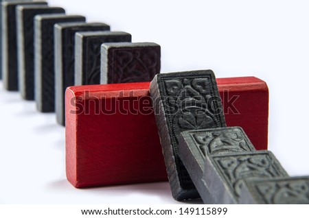 Red wooden wall preventing domino effect - stock photo
