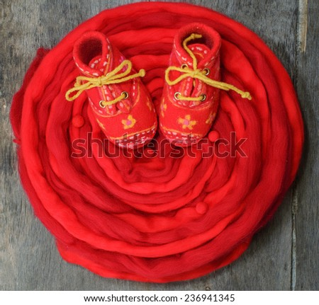 Red wool for felting and baby booties on the wooden background - stock photo