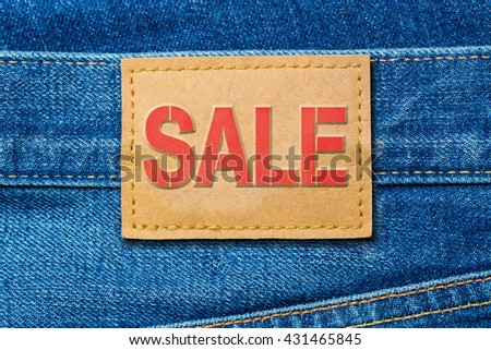 Red Word SALE on denim blue jeans fashion leather label background, close up - stock photo