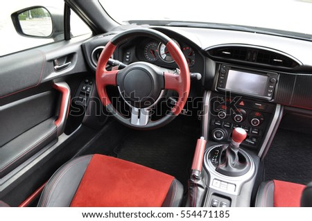 Red wrapped steering wheel and seats in the car interior