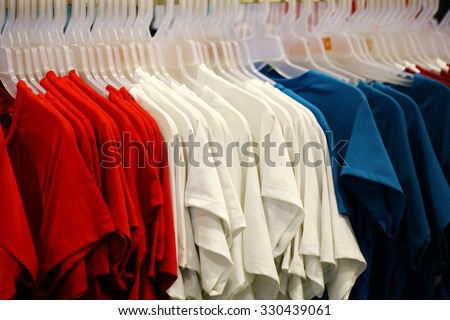 red write blue t-shirt in shop, French flag color,  looking through new clothes during shopping,Colorful women's dresses on wood hangers in a retail shop. Fashion and shopping business concept. team - stock photo