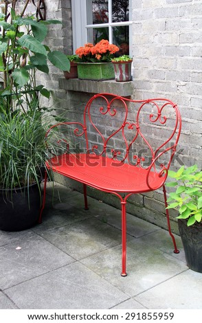 Red wrought iron bench outside on a garden patio.  - stock photo