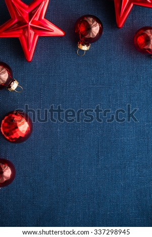 Red xmas decorations (stars and balls) on dark blue canvas background. Merry christmas card. Winter holiday theme. Space for text. Happy New Year. - stock photo