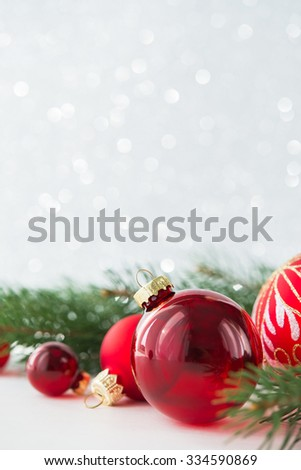 Red xmas ornaments on glitter holiday background. Merry christmas card. Winter theme. Happy New Year. Space for text. - stock photo