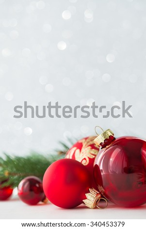 Red xmas ornaments on glitter holiday background. Merry christmas card. Winter theme. Happy New Year. Space for text.