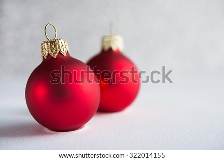 Red xmas ornaments on glitter holiday background. Winter holidays. Xmas theme. Copy space. - stock photo