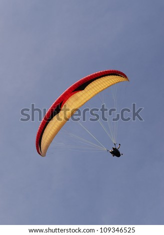 Red, yellow and black colored para glider gently turning in the sky. - stock photo