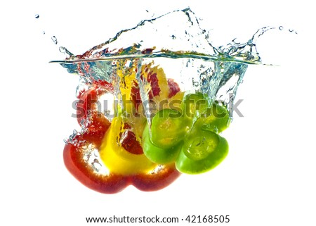 Red, yellow and green abstract pepper splashing in clear blue water - isolated against white background. - stock photo