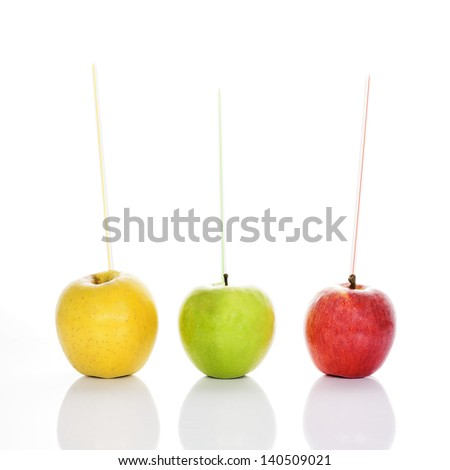 red, yellow and green apples with straws