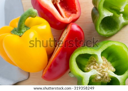Red, yellow, green bell pepper with knife on cutting board - stock photo