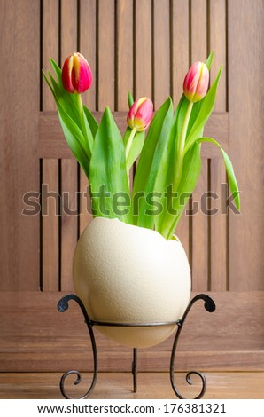 Red yellow tulips and easter  ostrich egg - stock photo