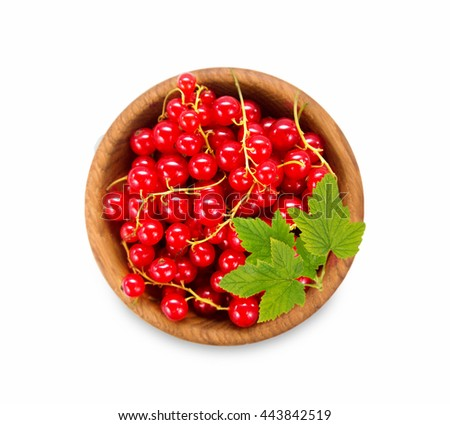 Redcurrant in a wooden bowl. Top view. Ripe and tasty currant isolated on white background. Red berries with leaves. - stock photo