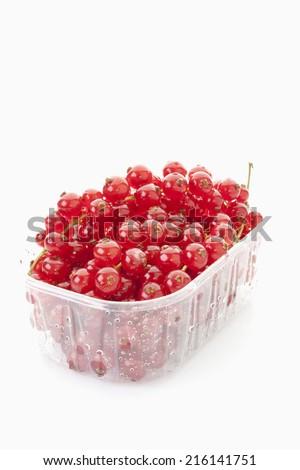 Redcurrant in plastic container - stock photo
