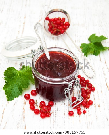 Redcurrants jam with fresh berries on a wooden background - stock photo
