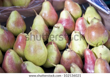 Reddish green pears in a padded brown plastic bag container.