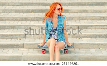 Redhair teen girl sitting on her skateboard against street stairs weared orange funky sunglasses. Pensive feelings. Outdoors, street fashion lifestyle. Beautiful young woman with a skate board - stock photo