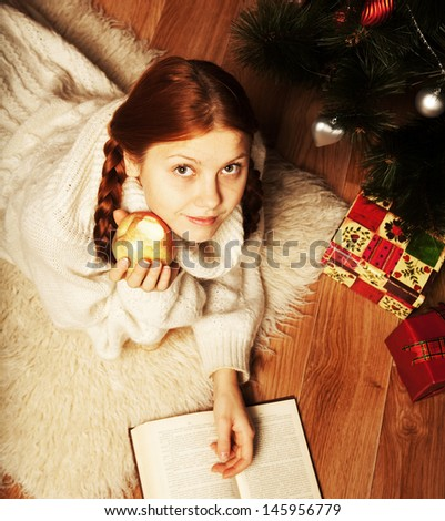 redhair woman reading book on Christmas in front of tree   - stock photo