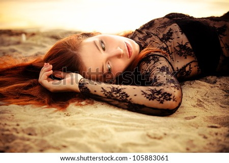 redhead beautiful woman on sand by the river - stock photo
