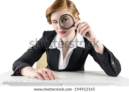Redhead businesswoman looking through magnifying glass on white background