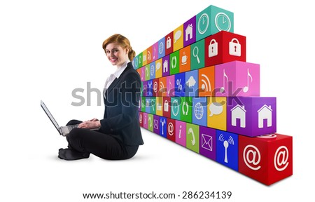 Redhead businesswoman using her laptop against app wall - stock photo