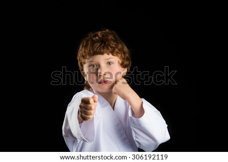 Redhead caucasian karate boy in white kimono isolated on black background
