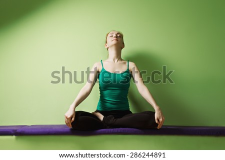redhead woman exercising yoga laying down stock photo