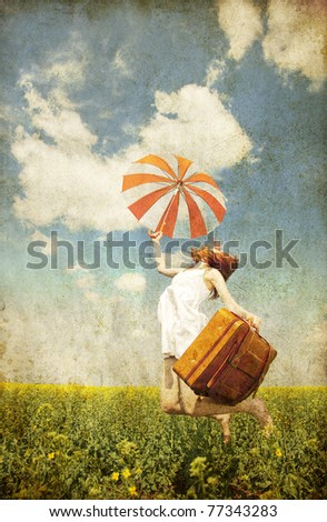 Redhead enchantress with umbrella and suitcase at spring rapeseed field. Photo in old image style. - stock photo