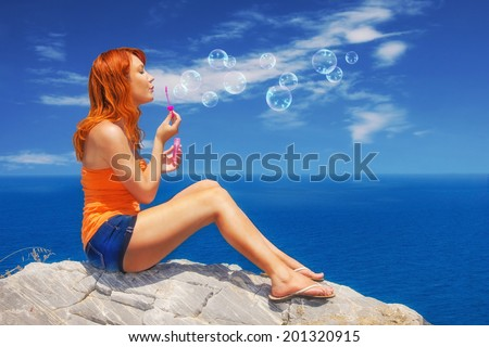 Redhead enjoying the view and blowing bubbles at Kastro, Skiathos - stock photo
