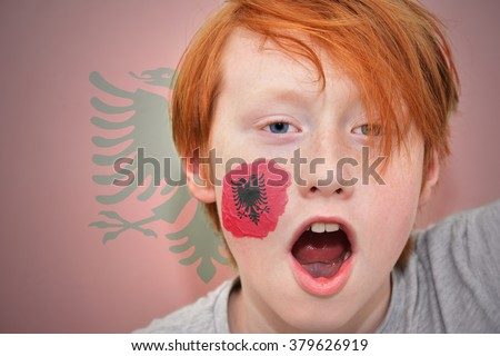 redhead fan boy with albanian flag painted on his face. on the albanian flag background - stock photo