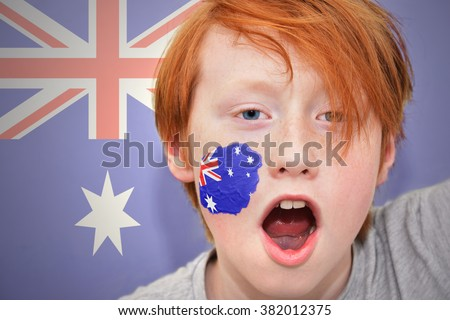 redhead fan boy with australian flag painted on his face. on the australian flag background - stock photo