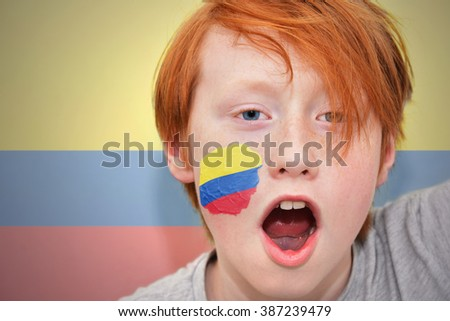 redhead fan boy with colombian flag painted on his face.  - stock photo